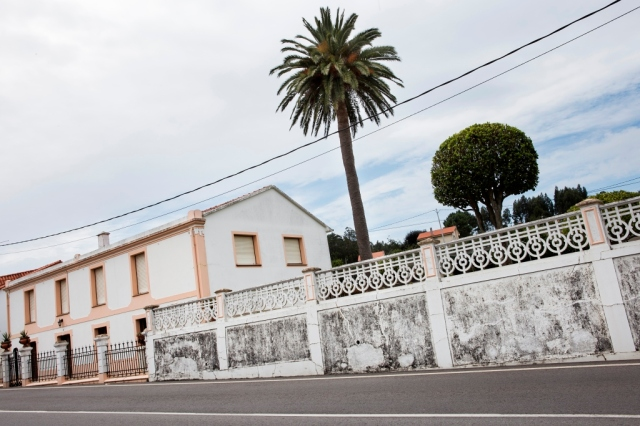 Sencilla casa situada al pie de la carretera que se dirige a Oleiros, a las afueras de Sada. El espacio, de planta rectangular y dos alturas, se abre en la fachada principal con ocho vanos recercados, los de la planta baja con acodos.